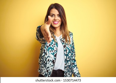 Young beautiful woman wearing casual jacket over yellow isolated background smiling friendly offering handshake as greeting and welcoming. Successful business.