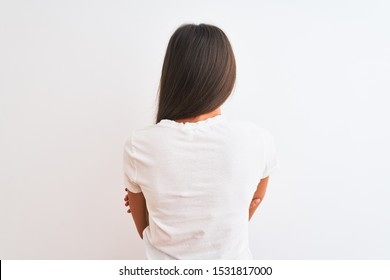 Young beautiful woman wearing casual t-shirt standing over isolated white background standing backwards looking away with crossed arms