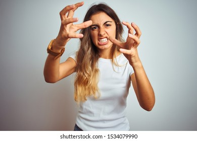 Young beautiful woman wearing casual white t-shirt over isolated background Shouting frustrated with rage, hands trying to strangle, yelling mad
