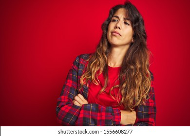 Young beautiful woman wearing casual jacket standing over red isolated background Surprised pointing with finger to the side, open mouth amazed expression.