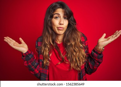Young beautiful woman wearing casual jacket standing over red isolated background Surprised pointing with hand finger to the side, open mouth amazed expression.