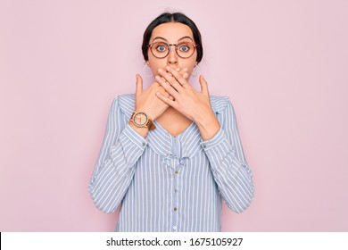 Young beautiful woman wearing casual striped shirt and glasses over pink background shocked covering mouth with hands for mistake. Secret concept.