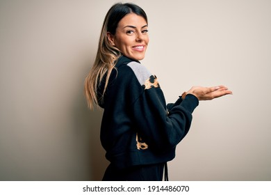 Young beautiful woman wearing casual sweatshirt standing over isolated white background pointing aside with hands open palms showing copy space, presenting advertisement smiling excited happy
