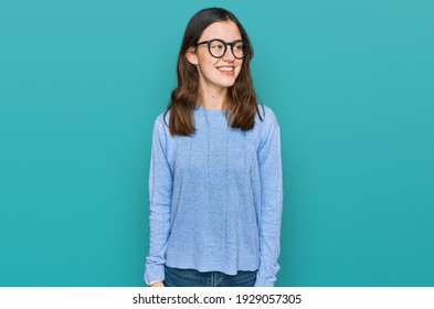 Young beautiful woman wearing casual clothes and glasses looking away to side with smile on face, natural expression. laughing confident.