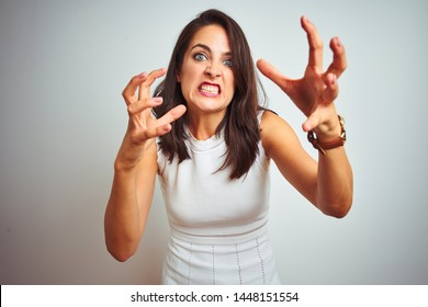 Young beautiful woman wearing dress standing over white isolated background Shouting frustrated with rage, hands trying to strangle, yelling mad