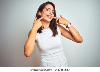 Young beautiful woman wearing dress standing over white isolated background smiling cheerful showing and pointing with fingers teeth and mouth. Dental health concept.