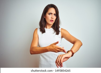 Young beautiful woman wearing dress standing over white isolated background In hurry pointing to watch time, impatience, upset and angry for deadline delay