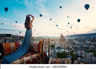 Young beautiful woman wearing elegant long dress in front of Cappadocia landscape at sunshine with balloons in the air. Turkey.
