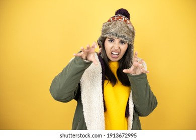 Young beautiful woman wearing a hat and a green winter coat over yellow background doing claw gesture as cat, aggressive and sexy expression