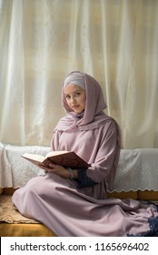 young beautiful woman wearing hijab sitting in room and holding Quran