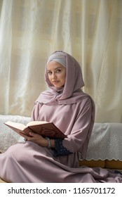young beautiful woman wearing hijab sitting and holding holly book