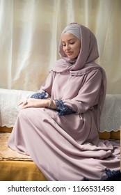 young beautiful woman wearing hijab sitting on sofa
