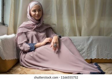 young beautiful woman wearing hijab sitting in comfort of sofa in house