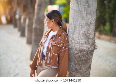 Young beautiful woman wearing jacket standing leaning on the palmtree at the town park