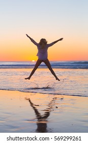 Young beautiful woman wearing jeans shorts and white t-shirt jumping on Cofete beach, Fuerteventura, Spain in sunset.