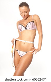 Young beautiful woman wearing lingerie with measure tape on white