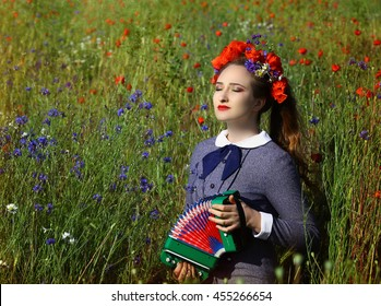 young beautiful woman wearing a poppy crown playing accordion in a flower field