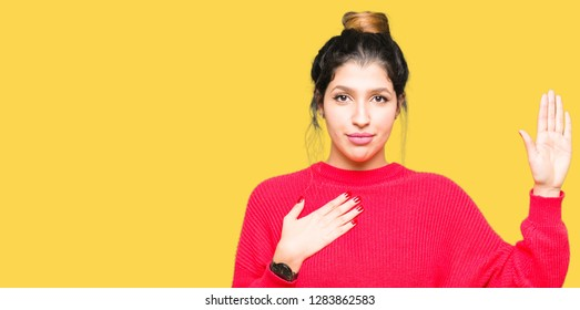 Young beautiful woman wearing red sweater and bun Swearing with hand on chest and open palm, making a loyalty promise oath