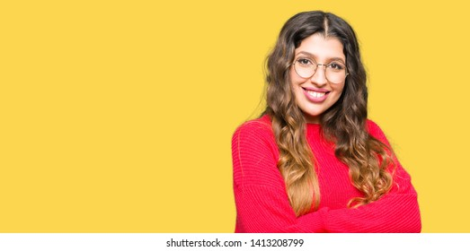 Young beautiful woman wearing red glasses happy face smiling with crossed arms looking at the camera. Positive person.