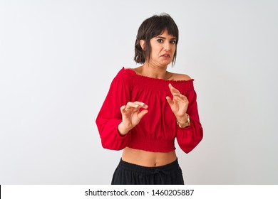 Young beautiful woman wearing red summer t-shirt standing over isolated white background disgusted expression, displeased and fearful doing disgust face because aversion reaction. With hands raised.
