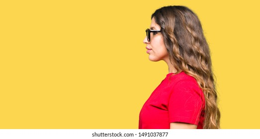 Young beautiful woman wearing red t-shirt and sunglasses looking to side, relax profile pose with natural face with confident smile.