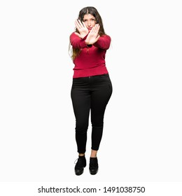 Young beautiful woman wearing red sweater Rejection expression crossing arms and palms doing negative sign, angry face