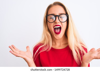 Young beautiful woman wearing red t-shirt and glasses standing over isolated white background celebrating mad and crazy for success with arms raised and closed eyes screaming excited. Winner concept