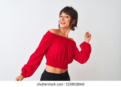 Young beautiful woman wearing red summer t-shirt standing over isolated white background Dancing happy and cheerful, smiling moving casual and confident listening to music