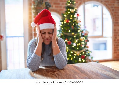 Young beautiful woman wearing santa claus hat at the table at home around christmas decoration suffering from headache desperate and stressed because pain and migraine. Hands on head.