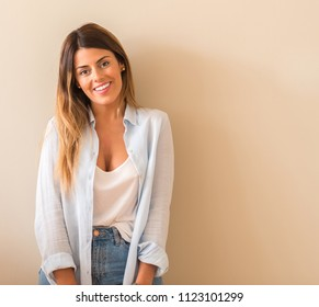 Young beautiful woman wearing a shirt smiling leaning on the wall at home and looking at the camera.