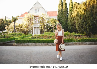 Young beautiful woman, wearing skirt, top and hat, walking in a blooming park among the greenery and the old palace with wisteria. Villa Kharaks (Haraks, Charax), Gaspra, Crimea, Russia. Manor, castle