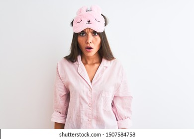 Young beautiful woman wearing sleep mask and pajama over isolated white background afraid and shocked with surprise and amazed expression, fear and excited face.