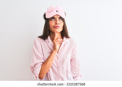 Young beautiful woman wearing sleep mask and pajama over isolated white background Thinking concentrated about doubt with finger on chin and looking up wondering