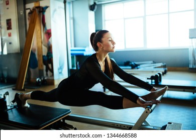 Young beautiful woman wearing sports clothing doing reformer exercises on pilates machine indoors in a studio