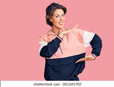 Young beautiful woman wearing sportswear gesturing with hands showing big and large size sign, measure symbol. smiling looking at the camera. measuring concept.