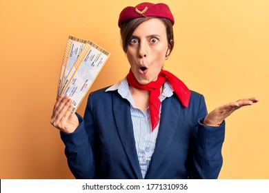 Young beautiful woman wearing stewardess uniform holding boarding pass scared and amazed with open mouth for surprise, disbelief face