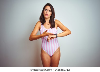Young beautiful woman wearing striped pink swimsuit swimwear over isolated background In hurry pointing to watch time, impatience, upset and angry for deadline delay