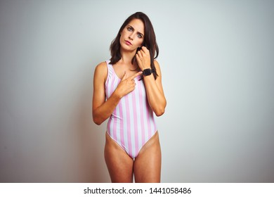 Young beautiful woman wearing striped pink swimsuit swimwear over isolated background In hurry pointing to watch time, impatience, looking at the camera with relaxed expression