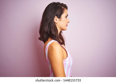 Young beautiful woman wearing striped pink swimsuit swimwear over pink isolated background looking to side, relax profile pose with natural face with confident smile.