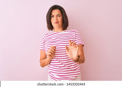 Young beautiful woman wearing striped t-shirt standing over isolated pink background disgusted expression, displeased and fearful doing disgust face because aversion reaction. With hands raised.