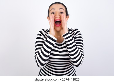 Young beautiful woman wearing stripped t-shirt against white background shouting excited to front.