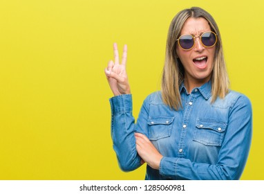 Young beautiful woman wearing sunglasses over isolated background smiling with happy face winking at the camera doing victory sign. Number two.