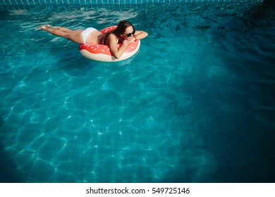Young beautiful woman wearing sunglasses relaxing in swimming pool with red rubber ring
