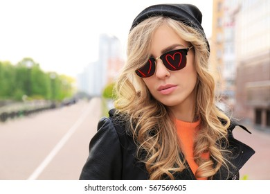 Young beautiful woman wearing sunglasses with hearts outdoor