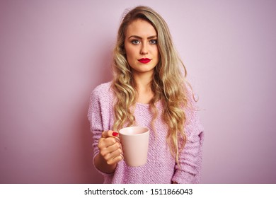 Young beautiful woman wearing sweater drinking a cup of coffee over pink isolated background with a confident expression on smart face thinking serious
