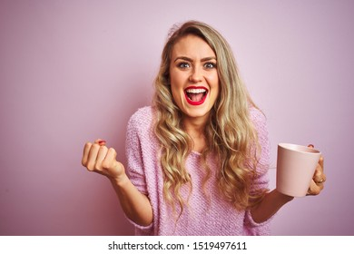 Young beautiful woman wearing sweater drinking a cup of coffee over pink isolated background screaming proud and celebrating victory and success very excited, cheering emotion