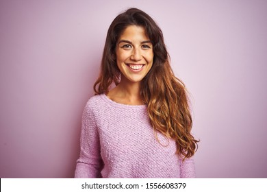 Young beautiful woman wearing sweater standing over pink isolated background with a happy and cool smile on face. Lucky person.
