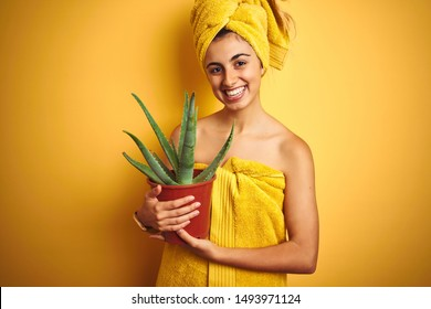 Young beautiful woman wearing a towel holding cactus pot over yellow isolated background with a happy face standing and smiling with a confident smile showing teeth