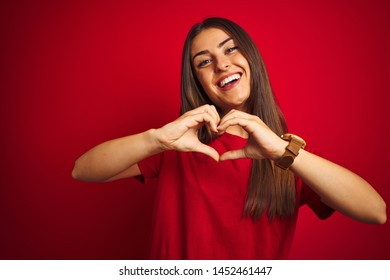 Young beautiful woman wearing t-shirt standing over isolated red background smiling in love doing heart symbol shape with hands. Romantic concept.