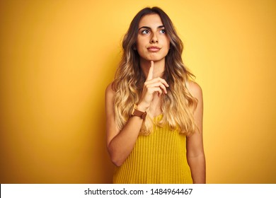 Young beautiful woman wearing t-shirt over yellow isolated background Thinking concentrated about doubt with finger on chin and looking up wondering